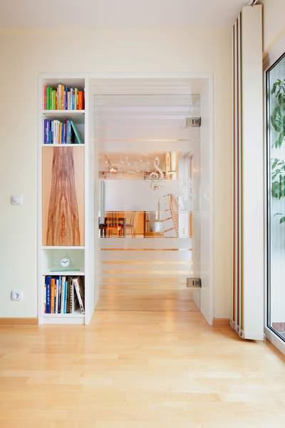 Raumteiler mit Glastür Auch in der Gestaltung des Bücherregals findet sich das charaktervolle Red Gum Holz wieder. Somit fügt sich auch dieses Element harmonisch in das Gesamtkonzept ein.
